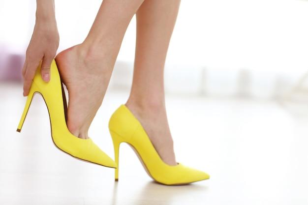 노란색 하이힐 신발을 벗는 여자.