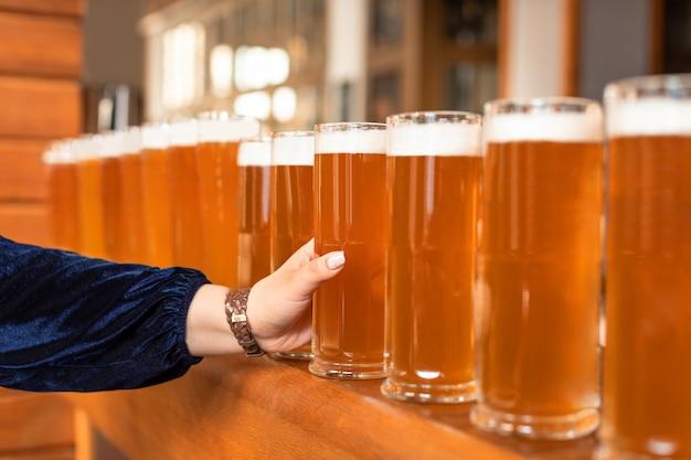 Женщина берет пивной бокал из большого количества вариантов