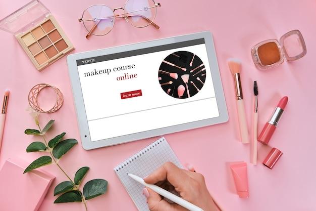 オンラインメイクアップトレーニングコースを受講し、タブレットでオンラインチュートリアルを見ている女性
