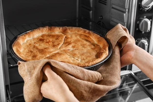 オーブンから焼きチキンポットパイを取り出す女性、クローズアップ