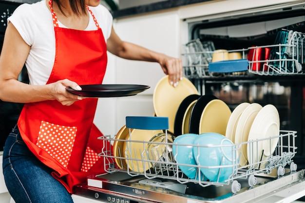 Женщина достает чистую посуду из посудомоечной машины.