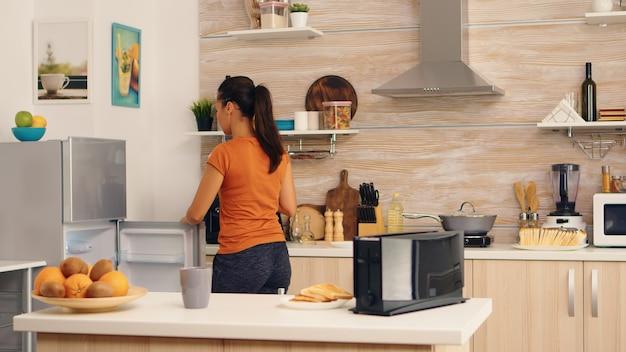 아침에 아침에 냉장고에서 계란을 꺼내는 여자. 주부는 부엌에 있는 냉장고에서 건강한 계란과 다른 재료를 얻고 있습니다.