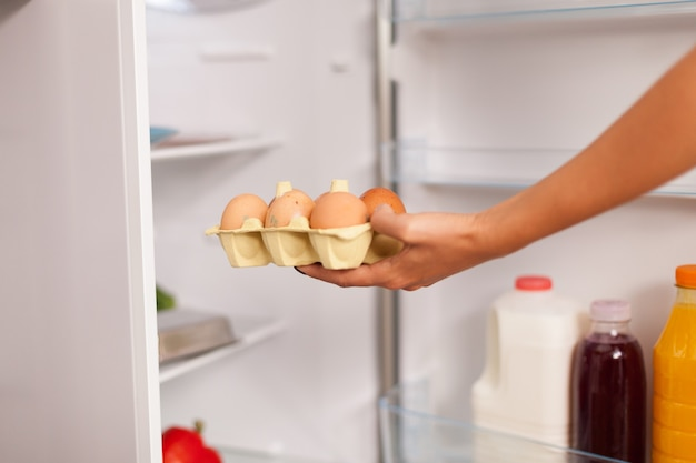 朝食のために朝冷蔵庫から卵を取り出す女性。キッチンの冷蔵庫からヘルシーな卵やその他の食材を手に入れる主婦。