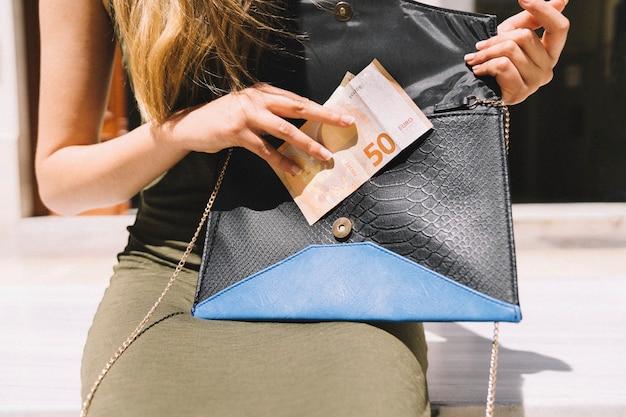 Женщина вынимает деньги из сумки