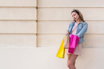 Woman taking out something from shopping bag at wall