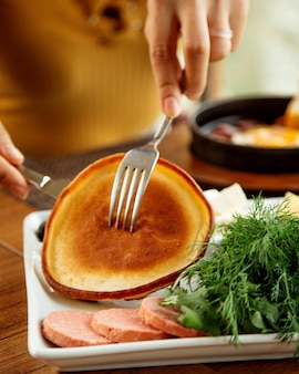 Woman taking pancake with fork and knife served for breakfast