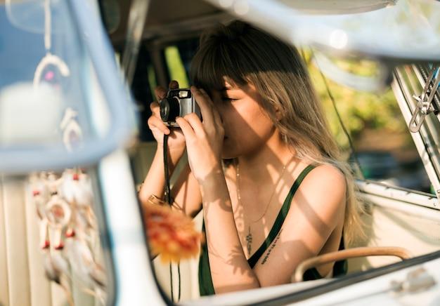 여행에 레트로 카메라로 사진을 찍는 여자