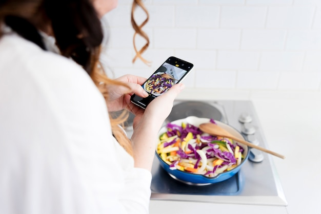 Woman taking photo of food in pan