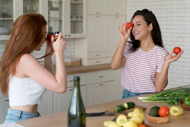 Woman taking a photo of her girlfriend in the kitchen