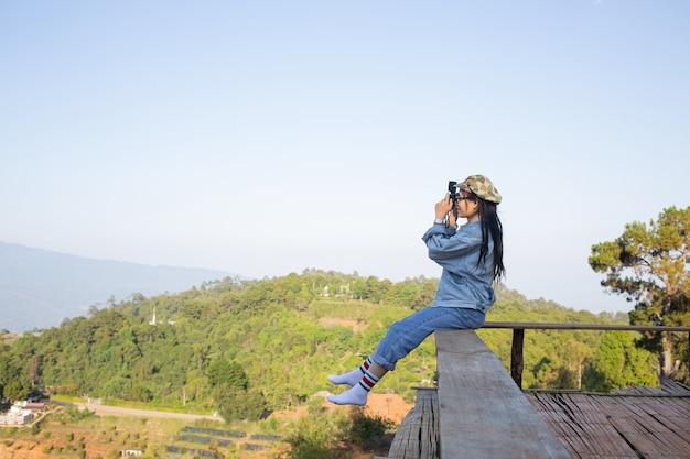 Женщина фотографирует посреди высоких деревьев в природе