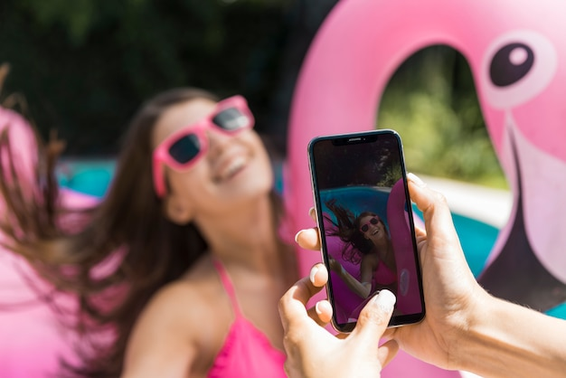 Woman taking photo laughing young female on inflatable flamingo in pool