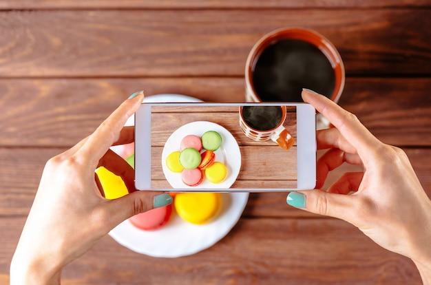 Woman taking photo of macarons dessert.