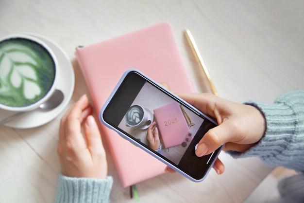 スマートフォンでブルーコーヒーラテ、ピンク色のプランナー2021、ゴールドペンの写真を撮る女性。人とテクノロジー。ソーシャルメディアに投稿して共有するために写真を撮る。ブログのコンセプト。