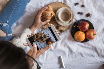 Woman taking photo of coffee and fruits with smartphone