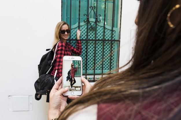 建物の近くの友人の写真を撮っている女性