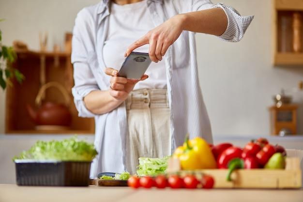 집에서 부엌, 음식 블로거 개념, 건강한 라이프 스타일에 그녀의 블로그에 대한 스마트 폰으로 건강한 샐러드의 여자 복용 사진.