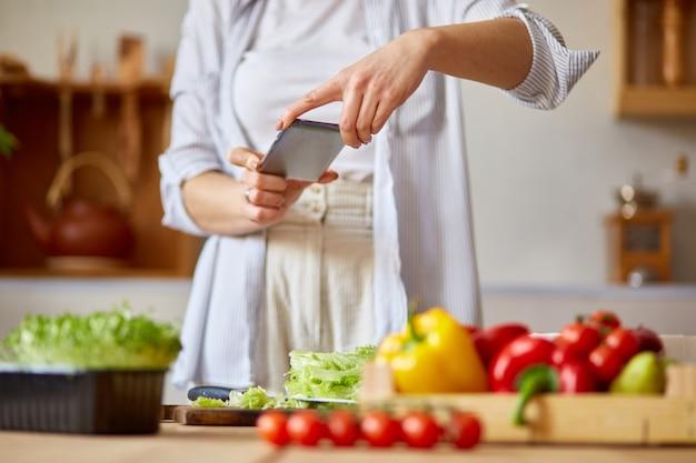 Женщина, делающая фото здорового салата со смартфоном для своего блога на кухне дома, концепция пищевого блоггера, здоровый образ жизни.