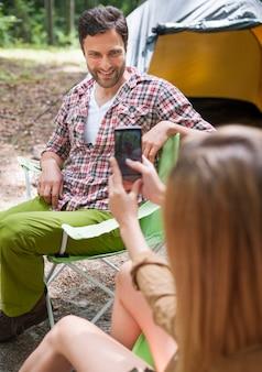Женщина фотографирует своего парня в лесу