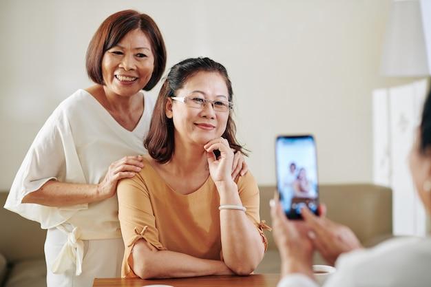 Женщина фотографирует своих довольно улыбающихся пожилых подруг