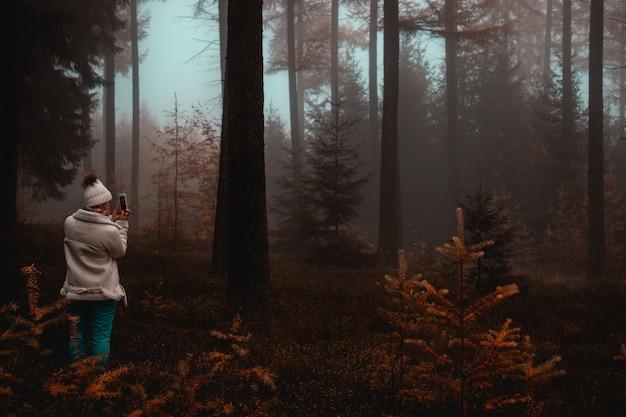Женщина, делающая фото дерева в лесу