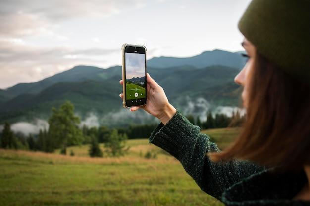 Donna che scatta una foto dei dintorni rurali