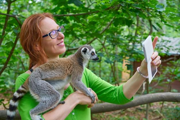 반지 꼬리가 달린 여우 원숭이와 사진 selfie를 복용하는 여자