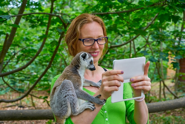 Woman taking photo selfie with ring tailed lemur