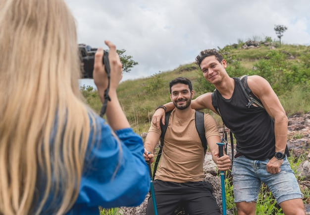 Woman taking a photo of two hiker man between a vacation mountain journey
