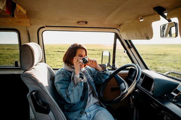 Woman taking a photo in a van