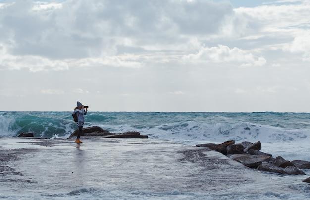 Женщина, принимая фото с пляжа камерин в дневное время с морем
