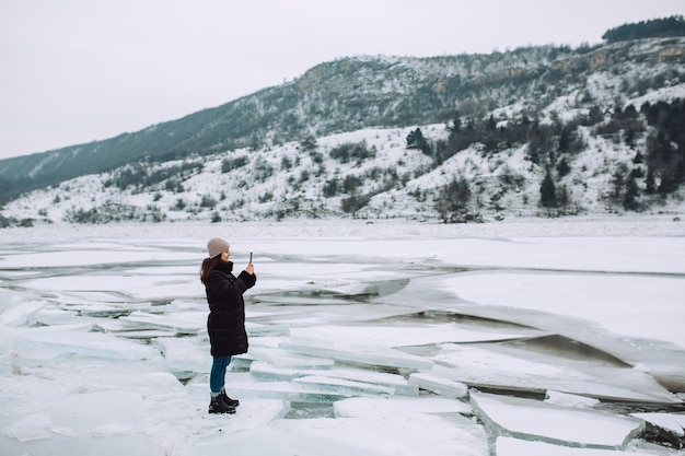 Woman taking photo with her smartphone at winter landscape with ice floes and snowy hill.