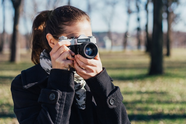 Woman taking a photo with old analog camera