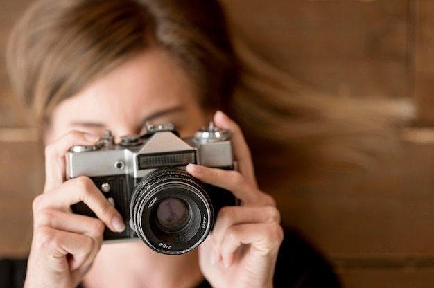 Woman taking a photo with retro camera close-up