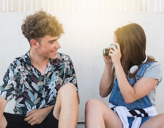 Woman taking photograph of her smiling boyfriend with camera