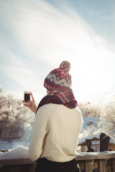 Woman taking a photograph using mobile phone at ski resort