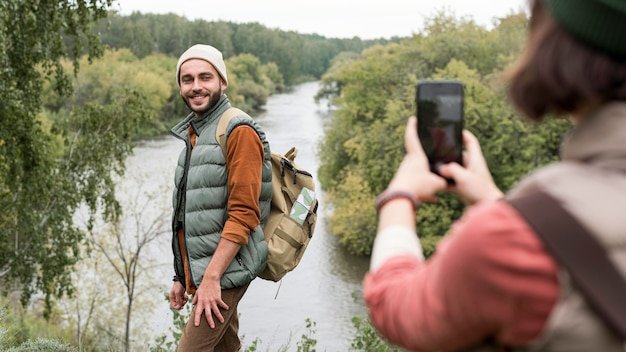 Woman taking photos of boyfriend in nature with smartphone