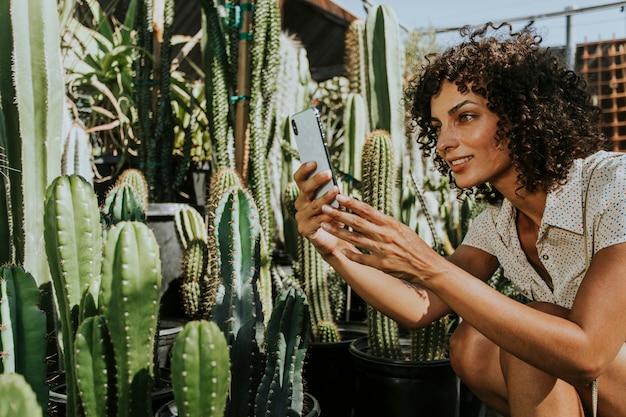 Woman taking photos of cacti at a botanical garden