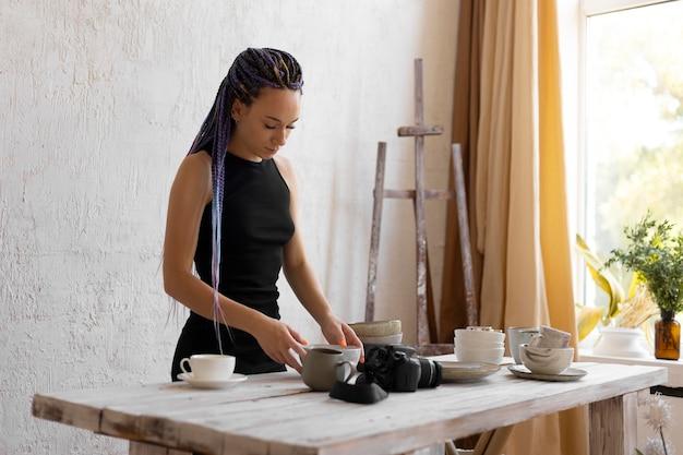 Woman taking photos of ceramic kitchenware at home