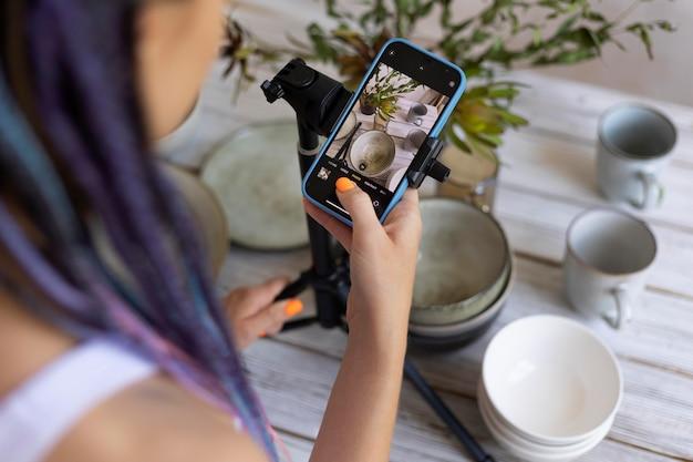 Donna che scatta foto di stoviglie in ceramica