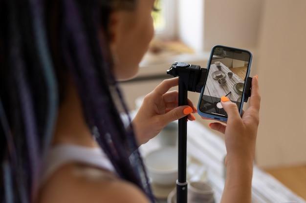 セラミック台所用品で彼女のビジネスのために写真を撮る女性