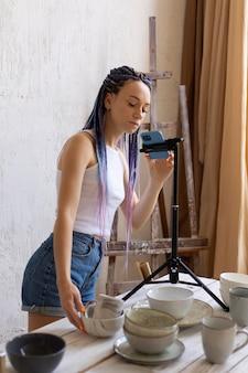 台所用品で彼女のビジネスのために写真を撮る女性