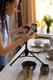 Donna che scatta foto per la sua attività con stoviglie in ceramica