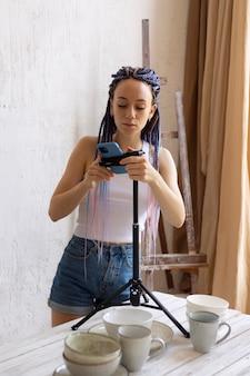 Donna che scatta foto per la sua attività con stoviglie