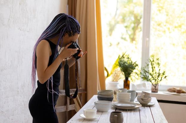 自宅でセラミック台所用品の写真を撮る女性
