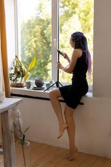 집에서 세라믹 주방용품 사진을 찍는 여성