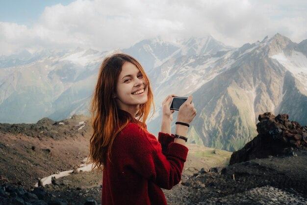 山の風景の写真を撮る女性