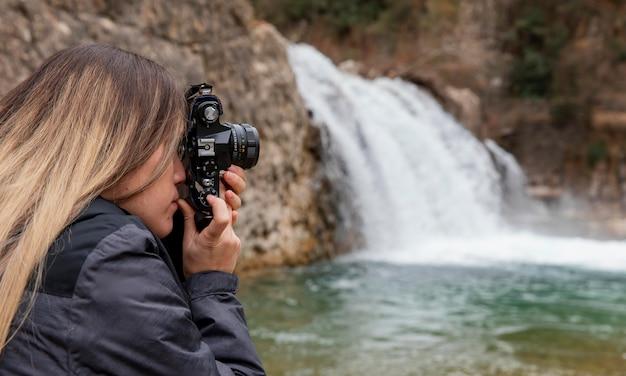 Женщина фотографирует природу