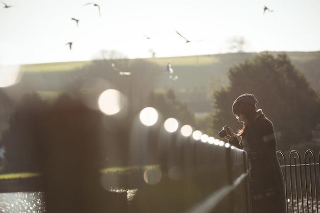 Женщина фотографирует на цифровой фотоаппарат в парке