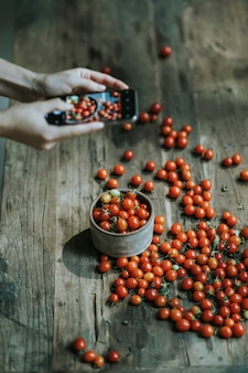 Woman taking photos of red cherry tomatoes