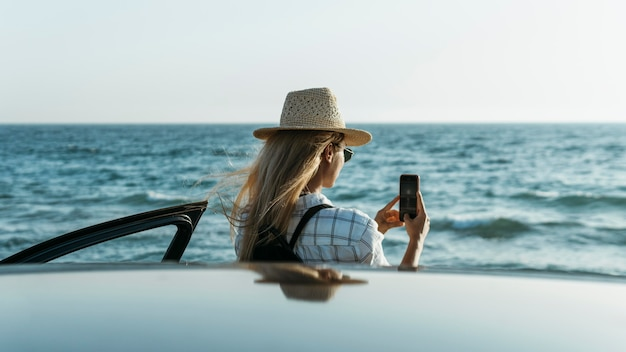 Woman taking photos of sea by car